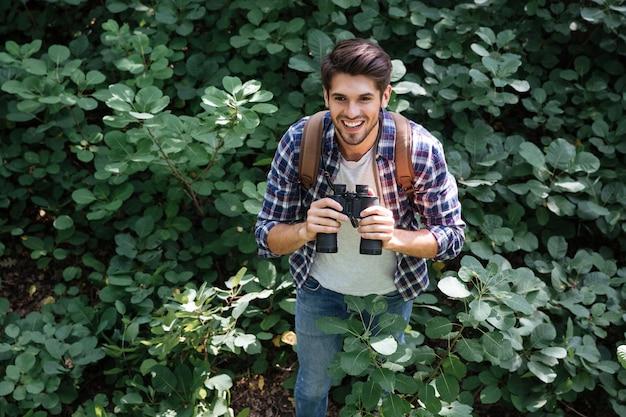 Vue de face de l'homme avec des jumelles en forêt