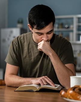 Vue de face de l'homme lisant la bible