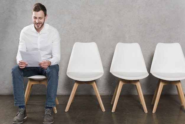 Vue de face d'un homme lisant son cv avant d'avoir son entretien d'embauche