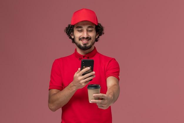 Vue de face homme livreur de courrier en chemise rouge et cape tenant une tasse de café de livraison marron et en prenant une photo sur le mur rose employé de livraison de services
