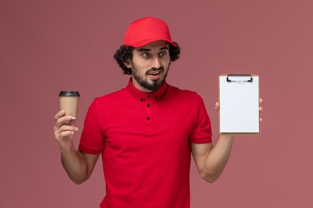 Vue de face homme livreur de courrier en chemise rouge et cape tenant une tasse de café marron et bloc-notes sur le mur rose clair employé de livraison uniforme de service