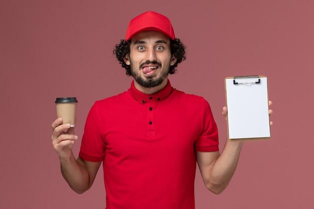 Vue de face homme livreur de courrier en chemise rouge et cape tenant une tasse de café marron et bloc-notes sur le mur rose clair employé de livraison uniforme de travail de service