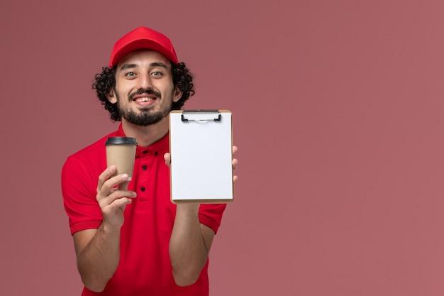 Vue de face homme livreur de courrier en chemise rouge et cape tenant une tasse de café marron et bloc-notes sur le mur rose clair service de livraison uniforme employé travailleur emploi