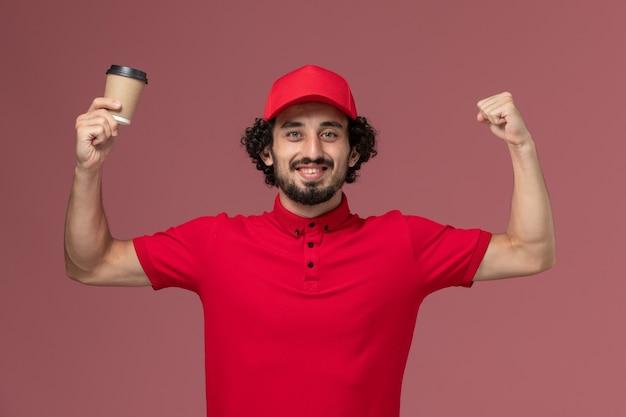Vue de face homme livreur de courrier en chemise rouge et cape tenant une tasse de café marron et souriant sur le mur rose clair employé de livraison uniforme de service