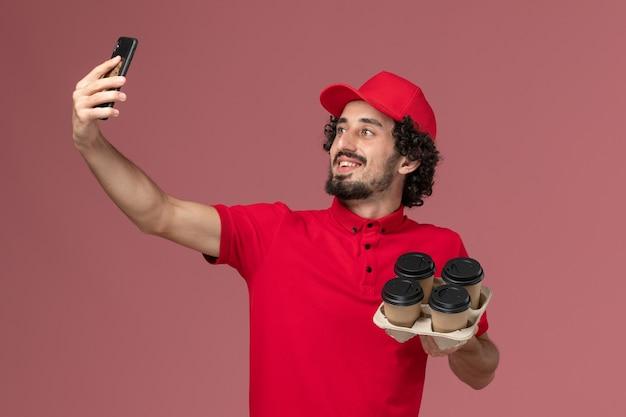Vue de face homme livreur de courrier en chemise rouge et cape tenant des tasses de café de livraison marron prenant selfie avec eux sur le mur rose clair employé de livraison de services