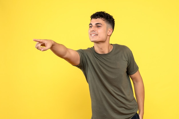 Vue de face un homme le mec souriant pointe un doigt sur le côté