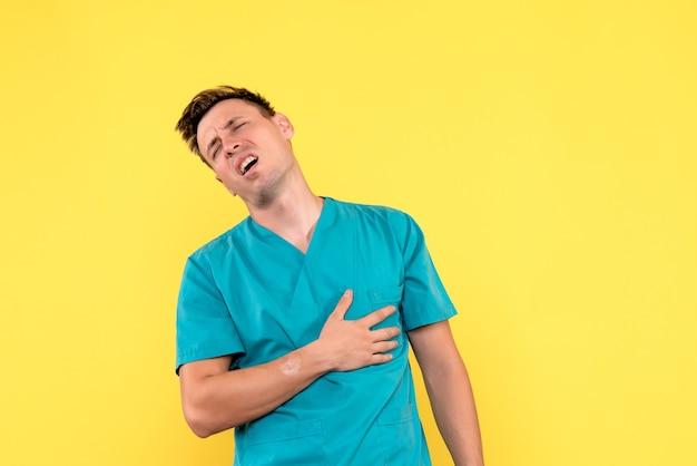 Vue de face de l'homme médecin ayant des problèmes cardiaques sur mur jaune