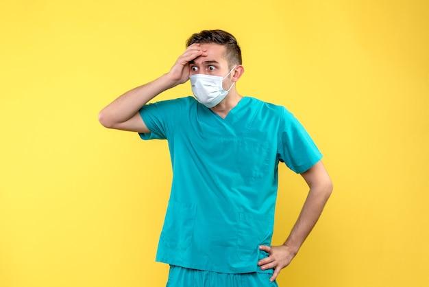 Vue de face de l'homme médecin choqué et effrayé mur jaune
