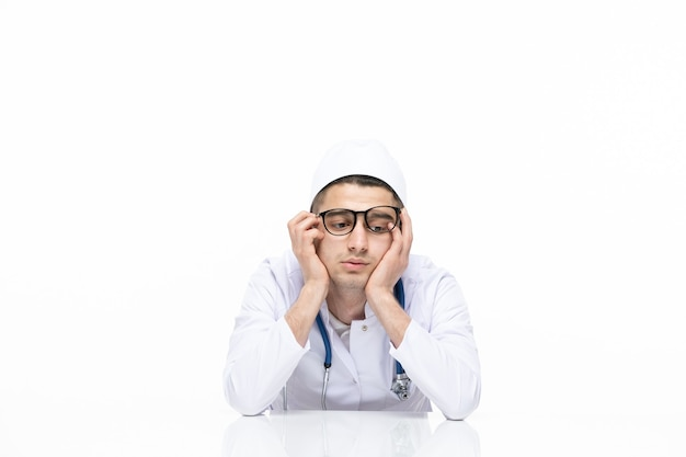 Vue de face de l'homme médecin en costume médical assis derrière un bureau