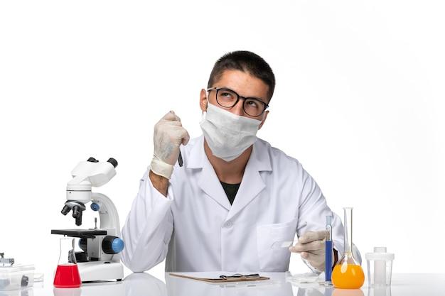 Vue de face de l'homme médecin en costume médical blanc travaillant et écrivant sur l'espace blanc