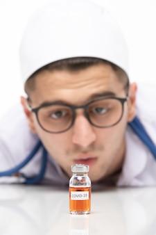 Vue de face de l'homme médecin en costume médical avec vaccin