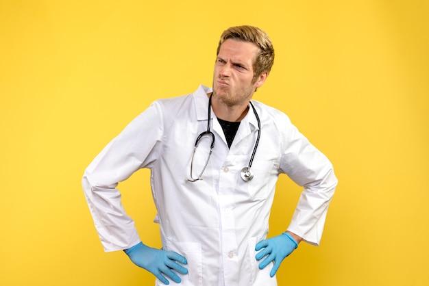 Vue de face de l'homme médecin sur fond jaune virus de la santé medic humain