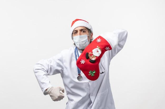 Vue de face de l'homme médecin avec grosse chaussette rouge sur le virus du mur blanc covid- vacances