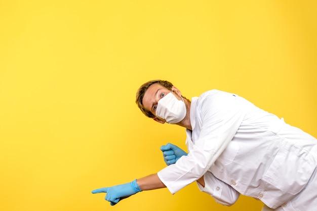 Vue de face de l'homme médecin en masque sur bureau jaune covid pandemic health medic