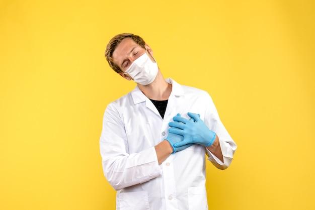 Vue de face de l'homme médecin en masque sur fond jaune pandémie médicale covid medic