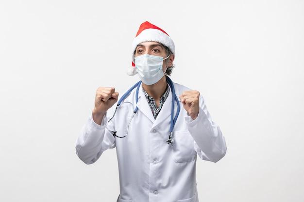 Vue de face de l'homme médecin avec masque sur plancher blanc virus pandémique covid vacances
