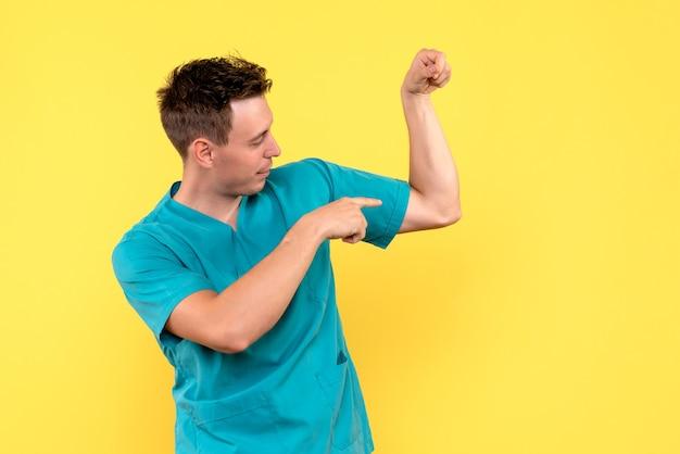Vue de face de l'homme médecin montrant sa force sur le mur jaune