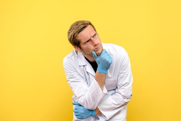 Vue de face de l'homme médecin pensant sur fond jaune covid- émotion médicale humaine