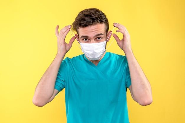 Vue de face de l'homme médecin portant un masque sur mur jaune
