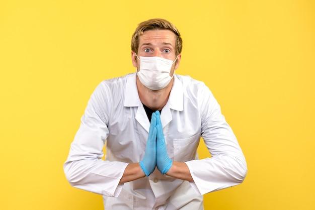 Vue de face de l'homme médecin en priant pose sur fond jaune pandémie medic health covid-