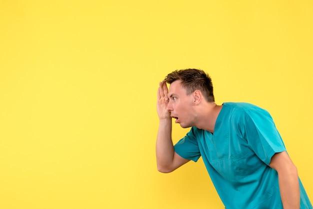 Vue de face de l'homme médecin regardant à travers les doigts sur le mur jaune
