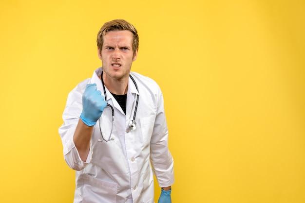 Vue de face de l'homme médecin se réjouissant sur fond jaune virus humain médical de la santé