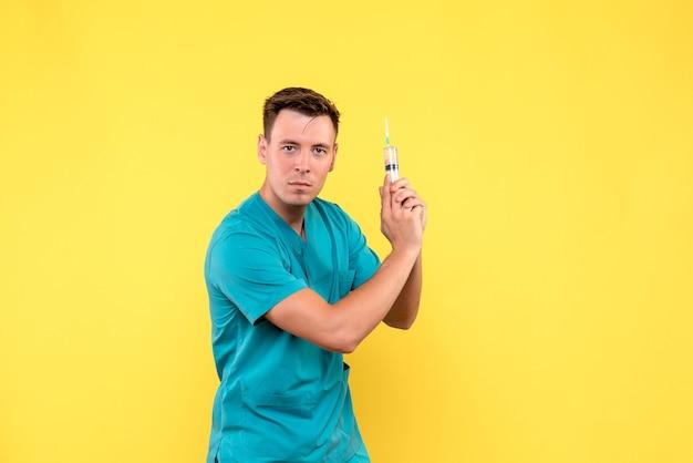 Vue de face de l'homme médecin tenant une énorme injection sur mur jaune