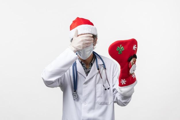 Vue de face de l'homme médecin tenant de grandes chaussettes de vacances sur le virus du mur blanc vacances covid