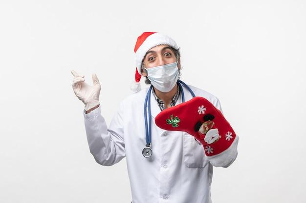 Vue de face homme médecin tenant grosse chaussette rouge sur blanc bureau virus covid- vacances