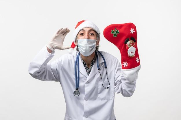 Vue de face de l'homme médecin tenant grosse chaussette rouge sur fond blanc virus covid- vacances