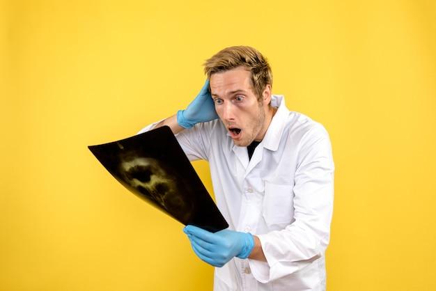 Vue de face de l'homme médecin tenant x-ray sur fond jaune chirurgie d'hygiène médicale covid