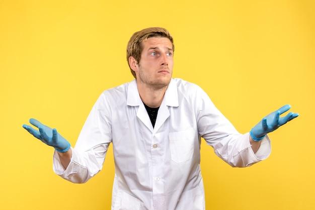 Vue de face de l'homme médecin avec visage confus sur fond jaune médecin humain covid- émotion