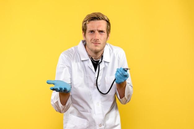 Vue de face de l'homme médecin avec visage confus sur fond jaune virus de la santé médicale émotion