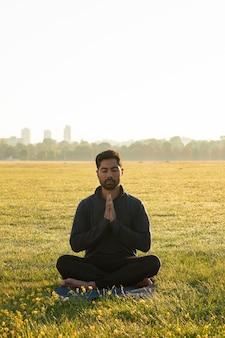 Vue de face de l'homme méditant à l'extérieur sur un tapis de yoga