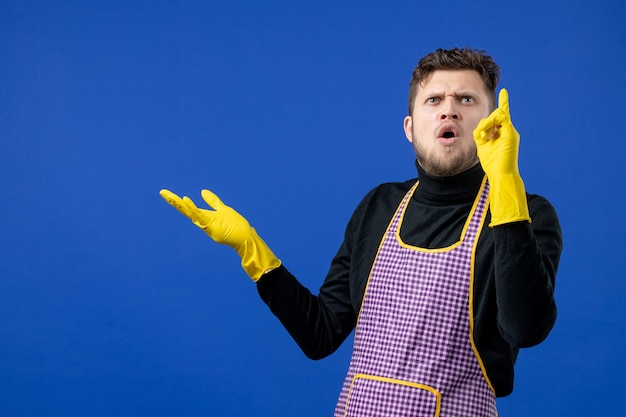 Vue de face de l'homme de ménage perplexe regardant le plafond sur le mur bleu