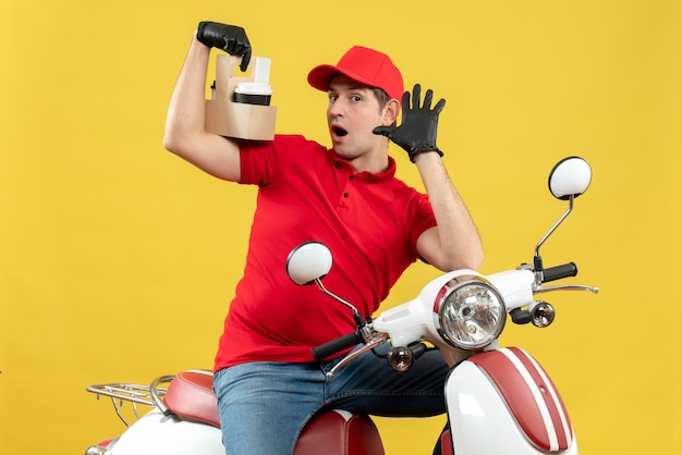 Vue de face de l'homme de messagerie choqué portant chemisier rouge et gants de chapeau dans un masque médical délivrant la commande assis sur un scooter axé sur les commandes