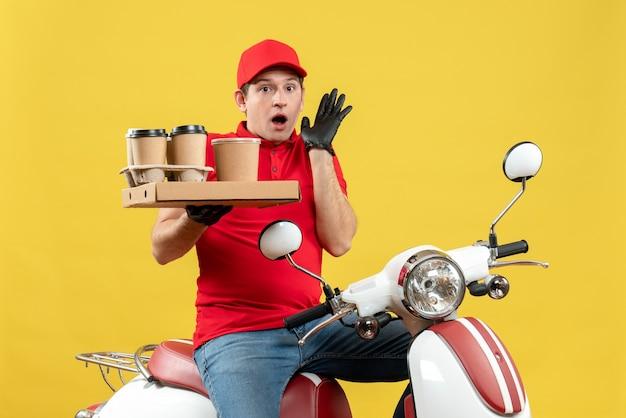 Vue de face de l'homme de messagerie choqué portant chemisier rouge et gants de chapeau en masque médical délivrant l'ordre assis sur les commandes de maintien de scooter