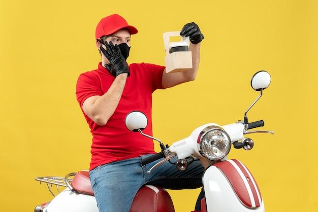 Vue de face de l'homme de messagerie ciblé surpris portant chemisier rouge et gants chapeau en masque médical assis sur un scooter