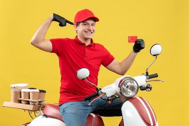 Vue de face de l'homme de messagerie souriant portant chemisier rouge et gants de chapeau en masque médical délivrant la commande assis sur la carte bancaire pointant scooter