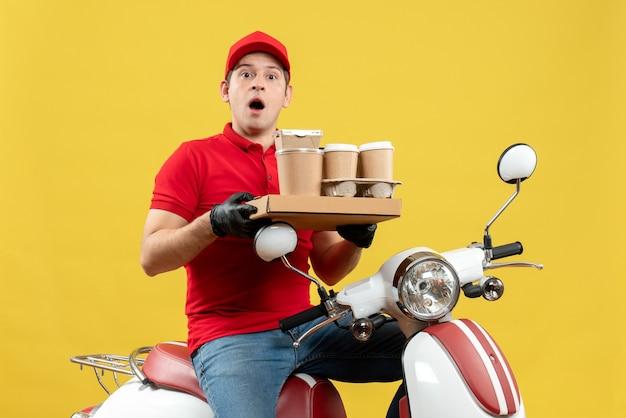 Vue de face de l'homme de messagerie surpris portant un chemisier rouge et des gants de chapeau dans un masque médical délivrant une commande assis sur des commandes de maintien de scooter