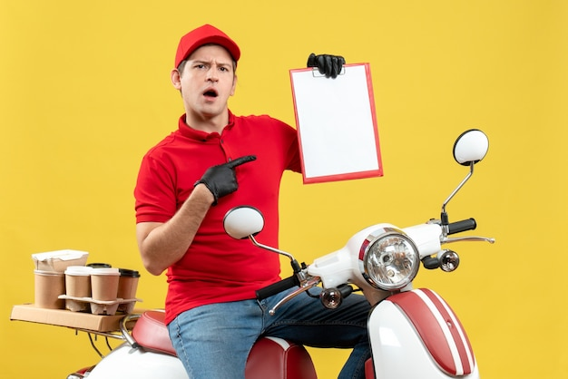 Vue de face de l'homme de messagerie surpris portant un chemisier rouge et des gants de chapeau dans un masque médical délivrant la commande assis sur le document tenant le scooter