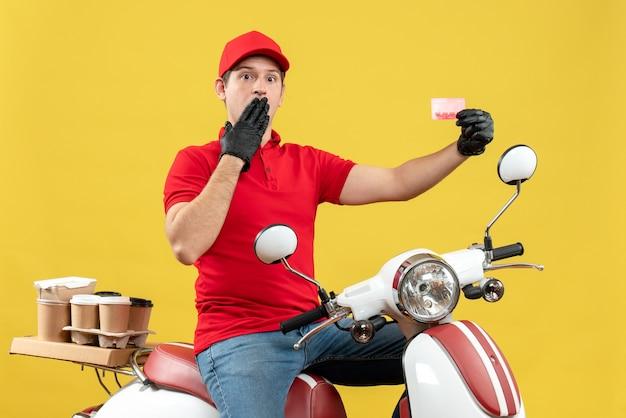 Vue de face de l'homme de messagerie surpris portant un chemisier rouge et des gants de chapeau dans un masque médical délivrant la commande assis sur un scooter tenant une carte bancaire