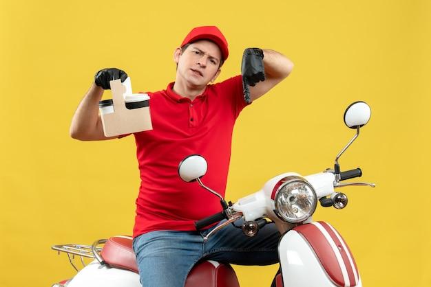 Vue de face de l'homme de messagerie surpris portant un chemisier rouge et des gants de chapeau dans un masque médical délivrant l'ordre assis sur des commandes de maintien de scooter pointant vers le bas