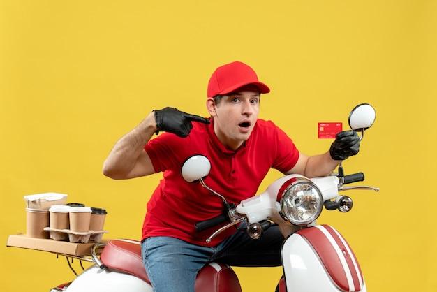 Vue de face de l'homme de messagerie surpris portant un chemisier rouge et des gants de chapeau en masque médical délivrant l'ordre assis sur la carte bancaire pointant scooter