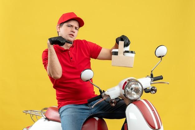 Vue de face de l'homme de messagerie surpris portant un chemisier rouge et des gants de chapeau en masque médical délivrant l'ordre assis sur les commandes de pointage de scooter