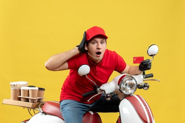 Vue de face de l'homme de messagerie surpris portant un chemisier rouge et des gants de chapeau en masque médical délivrant l'ordre assis sur un scooter montrant une carte bancaire