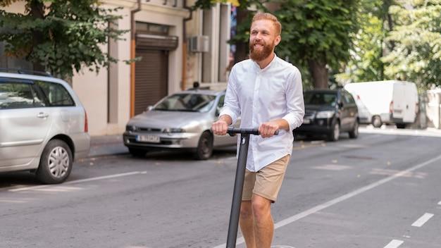 Vue de face homme moderne barbu sur scooter à l'extérieur