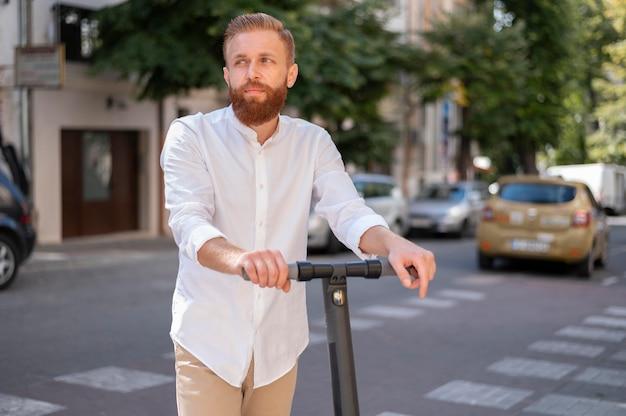 Vue de face homme moderne barbu sur scooter