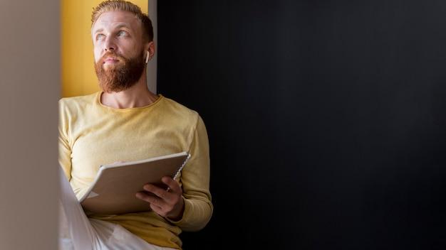 Vue de face homme moderne tenant ses notes avec copie espace