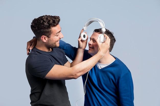 Vue de face homme montrant à son ami une chanson avec des écouteurs